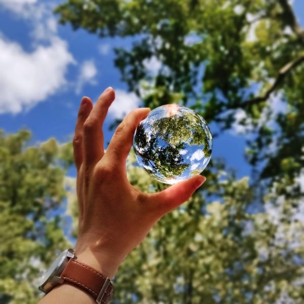 unknown person holding clear glass ball
